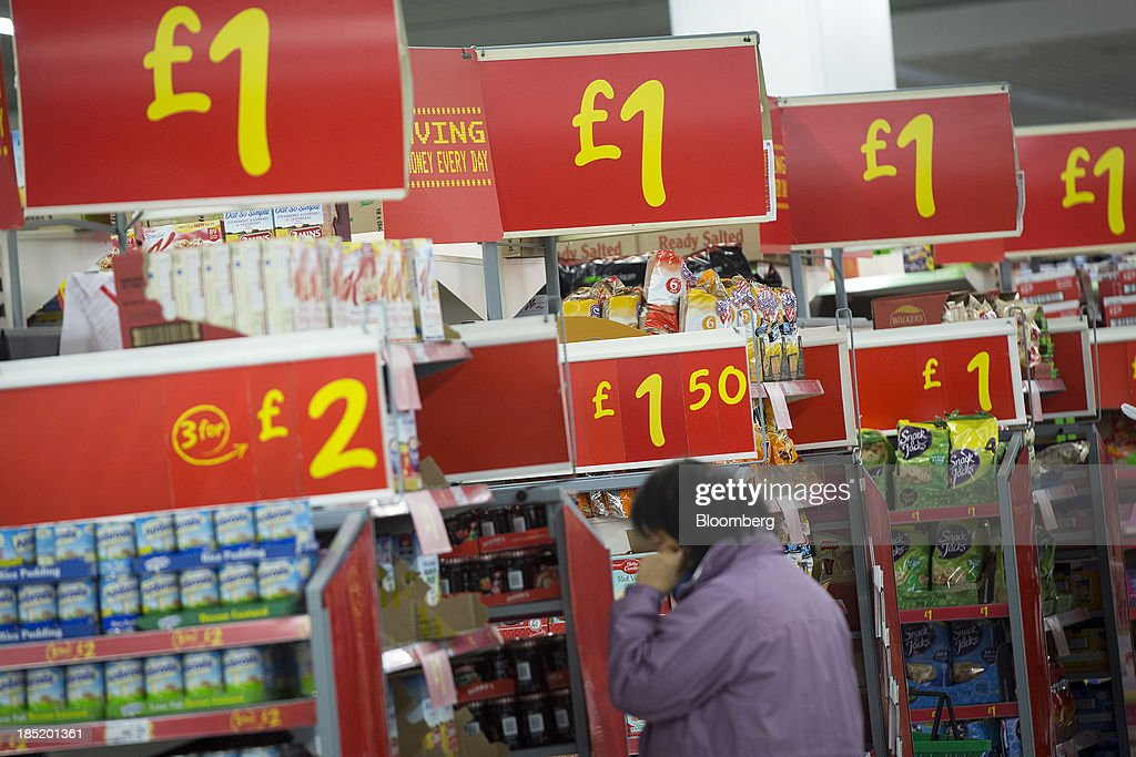Giant signs advertise the cost of discounted goods inside an Asda supermarket, the U.K. retail arm of Wal-Mart Stores Inc., in Watford, U.K., on Thursday, Oct. 17, 2013. U.K. retail sales rose more than economists forecast in September as an increase in furniture demand led a rebound from a slump the previous month. Photographer: Simon Dawson/Bloomberg via Getty Images