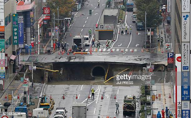 A giant sinkhole is seen in a fivelane urban boulevard exposing support columns of nearby buildings at a traffic intersection in Fukuoka southwestern...