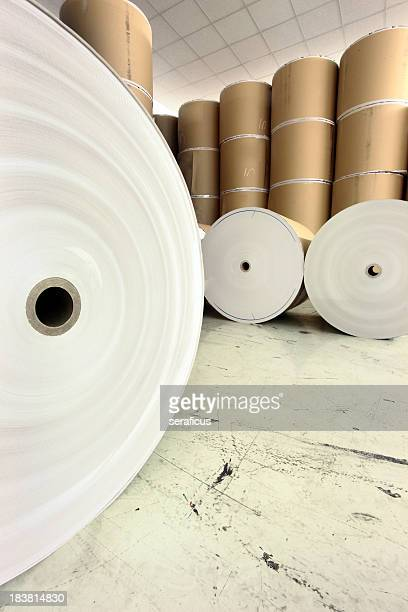 Giant spools of raw paper stacked in a warehouse