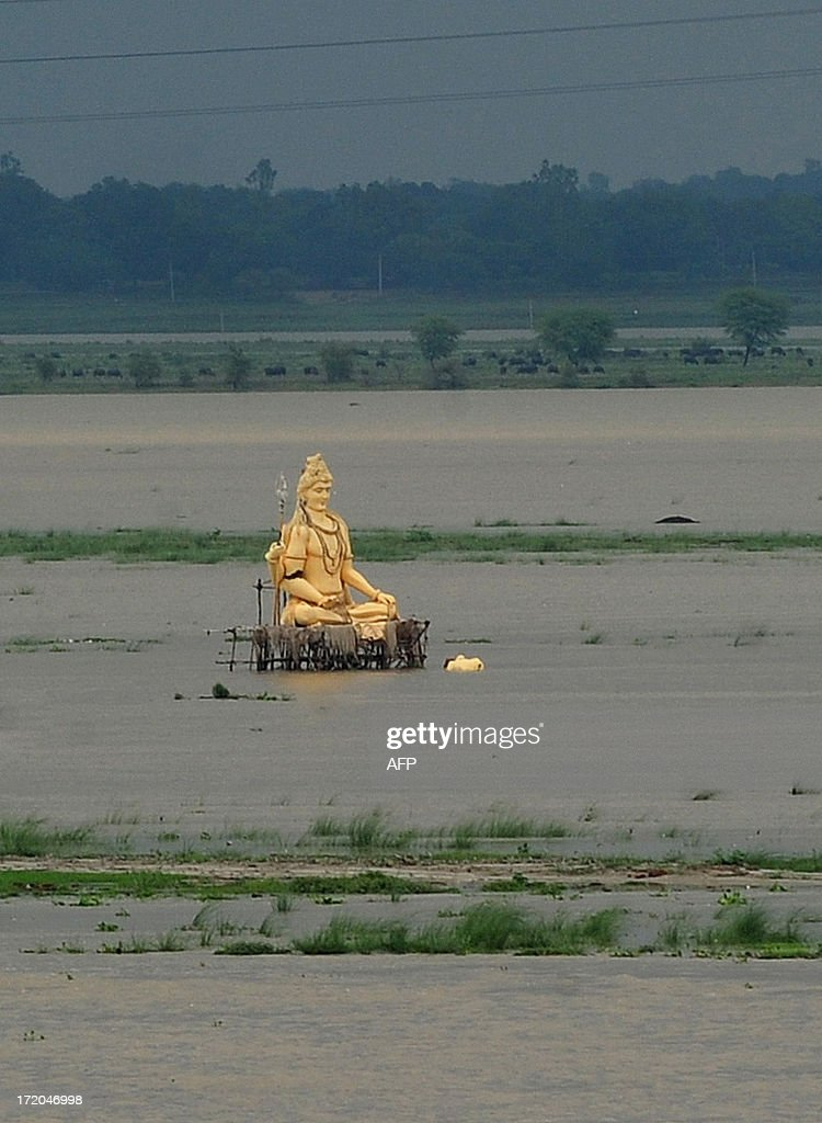 A giant statue of Hindu god Lord Shiva is partially submerged in floodwaters near the Ganges river as the water level of the Ganges and Yamuna rivers rises in Allahabad on July 1, 2013. Construction along river banks will be banned in the devastated north Indian state of Uttarakhand amid concerns unchecked development fuelled June's flash floods and landslides that killed thousands, the state's top official said July 1.