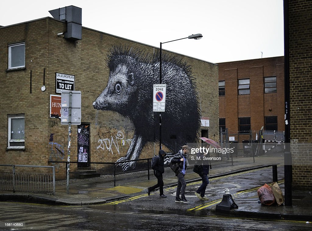 A giant street art piece on a brick wall in Shoreditch, East London. The art work is by the Dutchman Roa. Three male young hip pedestrians walk past. It is raining.