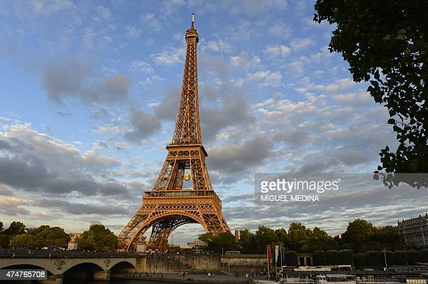 A giant tennis ball hangs under the Eiffel Tower on the sidelines of the Roland Garros 2015 French Tennis Open in Paris on May 25 2015 AFP PHOTO /...
