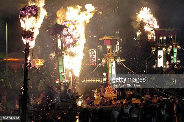 Giant torches march on next to 'Kiriko' floats during the Noto Abare festival on July 1 2005 in Noto Ishikawa Japan