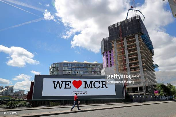 A giant TV screen displays the 'We Love Manchester logo and police emergency incident telephone number after last nights terrorist attack May 23 2017...