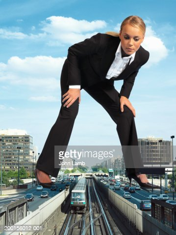 Giant woman standing over train on tracks (Digital Composite)