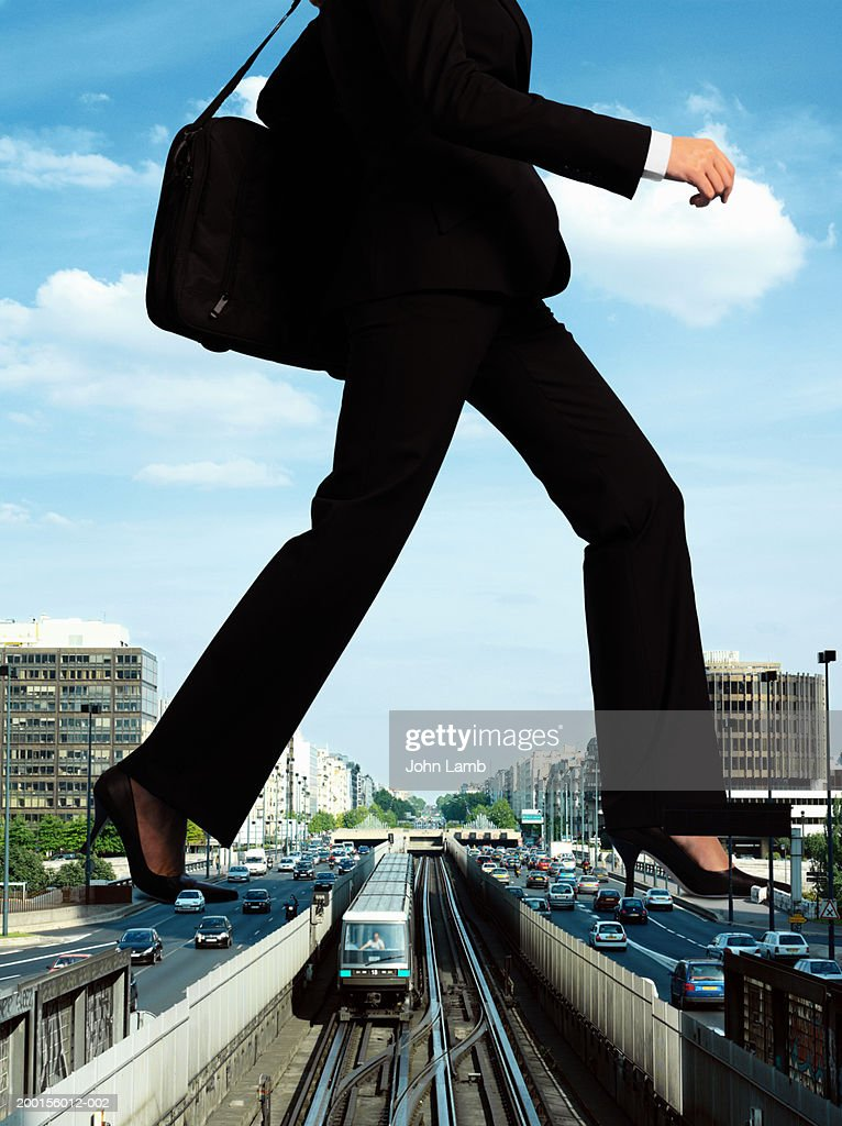 Giant woman stepping over train on tracks (Digital Composite) : Stock Photo