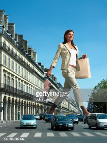 Giant woman with shopping bags crossing busy road (Digital Composite)