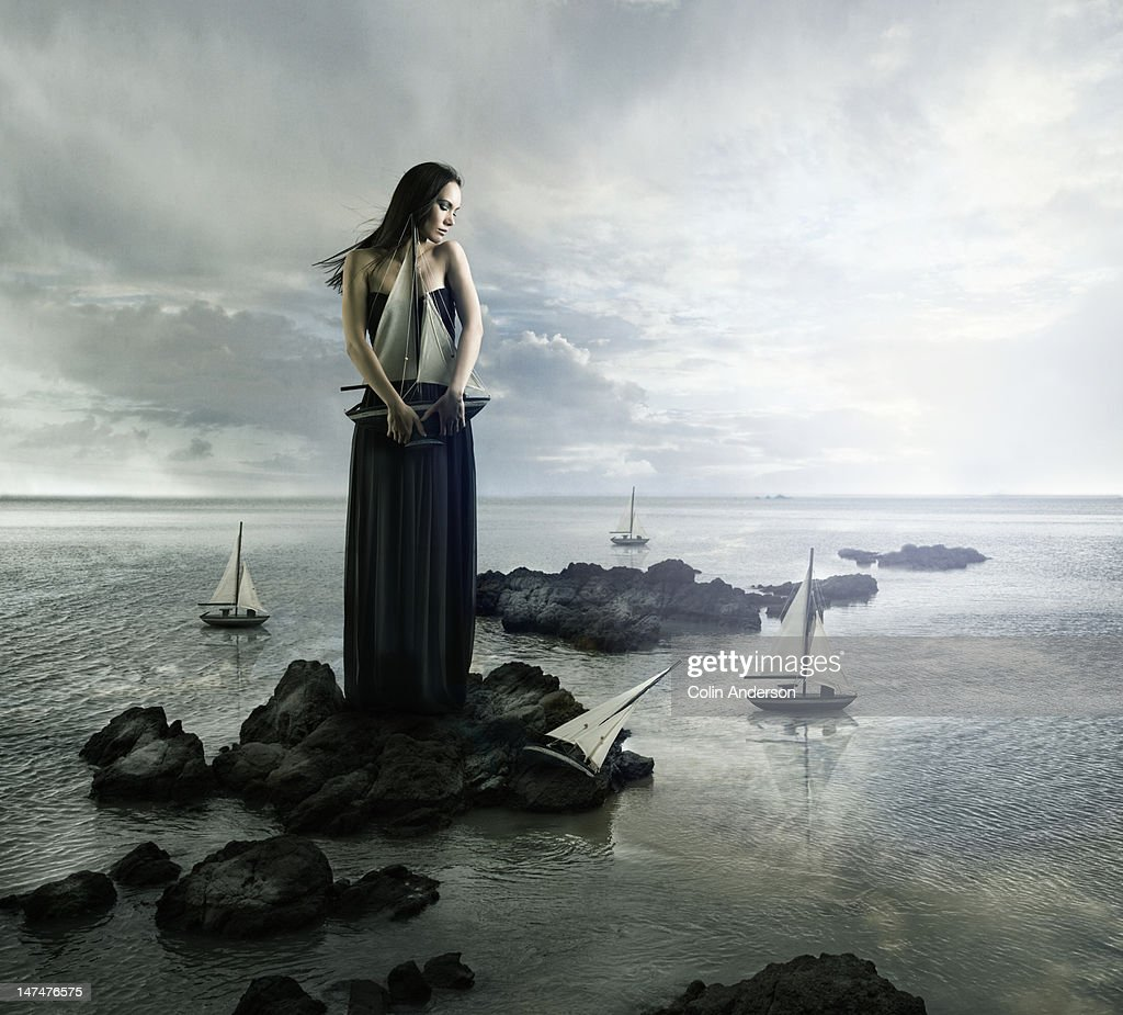 Giantess standing on rocks, clutching a boat : Stock Photo