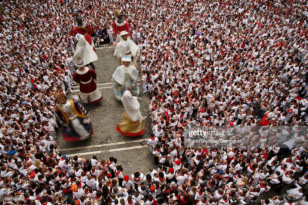 Giants figures dance surrounded by children and revellers during the farewell ceremony of the Comparsa de Gigantes y Cabezudos 'Giants and Big Heads parade' at the Town Hall Square on the final day of the San Fermin Running Of The Bulls festival on July 14, 2014 in Pamplona, Spain. The annual Fiesta de San Fermin, made famous by the 1926 novel of US writer Ernest Hemingway 'The Sun Also Rises', involves the running of the bulls through the historic heart of Pamplona.