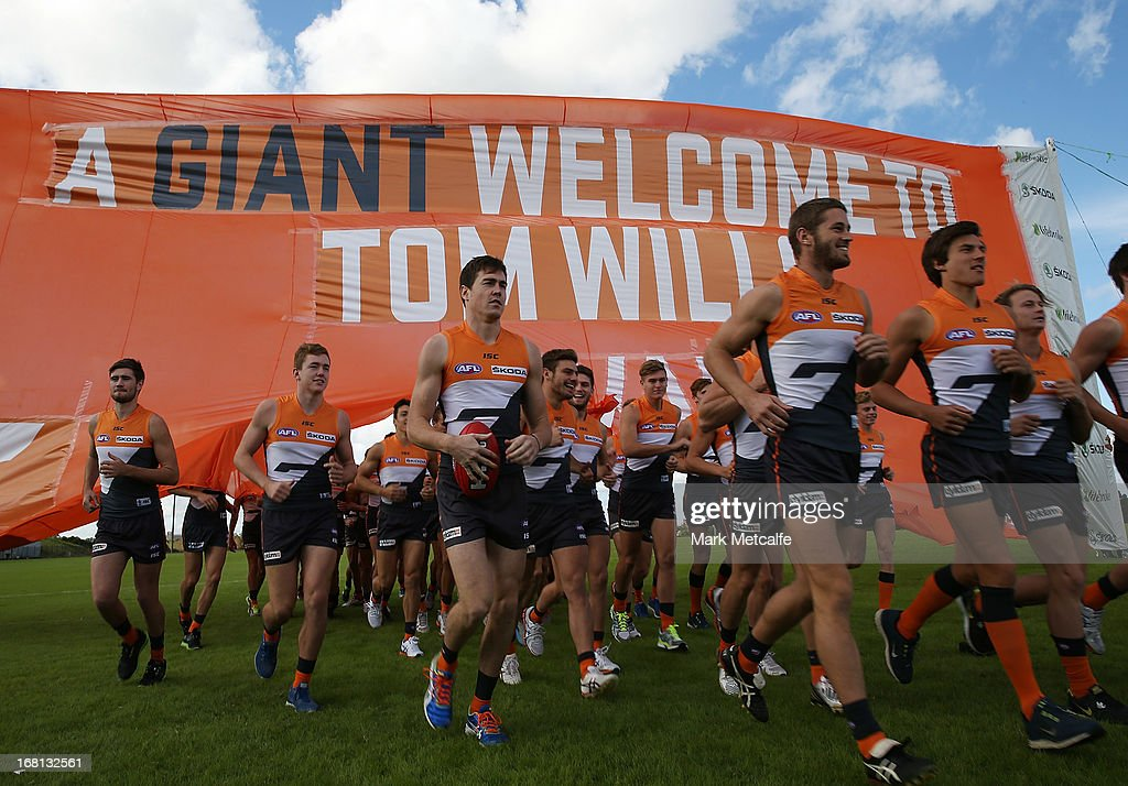 Giants players run through a banner during a GWS Giants AFL media session at Sydney Olympic Park Sports Centre on May 6, 2013 in Sydney, Australia.