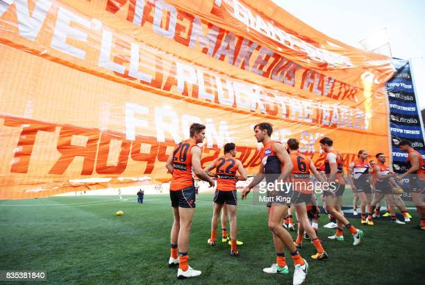 Giants walk through their banner during the round 22 AFL match between the Greater Western Sydney Giants and the West Coast Eagles at Spotless...