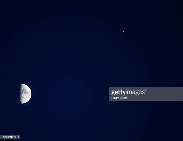 Gibbous moon and lonely star in night sky