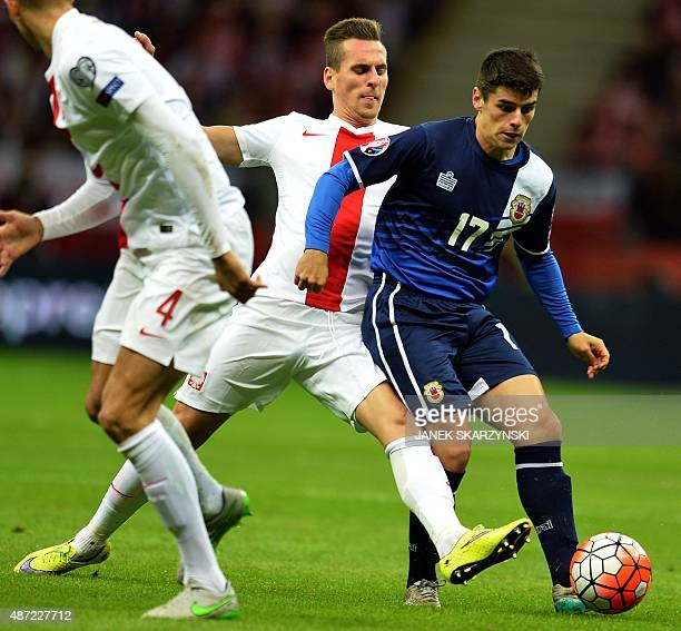 Gibraltar's Anthony Bardon and Poland's Arkadiusz Milik vie for the ball during the UEFA Euro 2016 qualifying football match between Poland and...