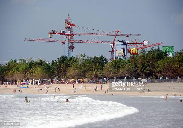 GIBSONIn this photograph taken on February 2 tourists flock to Kuta Beach on the resort island of Bali while in the background construction cranes...
