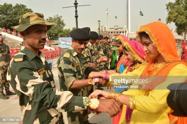 Giddha girls tying rakhi on the wrists of Border Security Force Jawans on the occasion of Raksha Bandhan festival at Attar Border near on August 7...