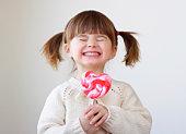 Beautiful little girl holding a big heart shaped lollipop