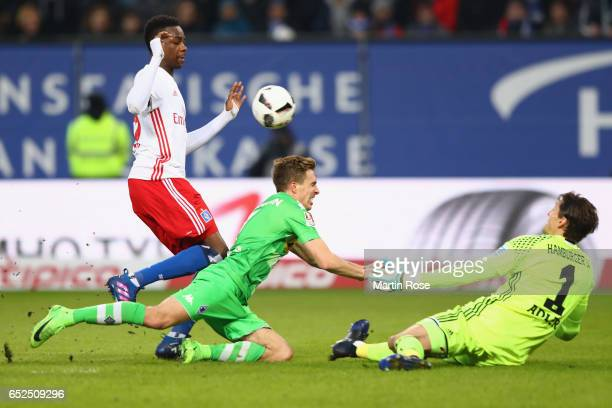 Gideon Jung of Hamburg and his keeper Rene Adler battle for the ball with Patrick Hermann of Moenchengladbach during the Bundesliga match between...
