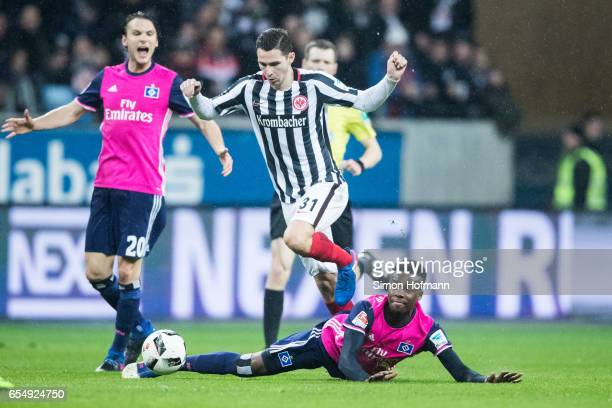 Gideon Jung of Hamburg is challenged by Branimir Hrgota of Frankfurt during the Bundesliga match between Eintracht Frankfurt and Hamburger SV at...