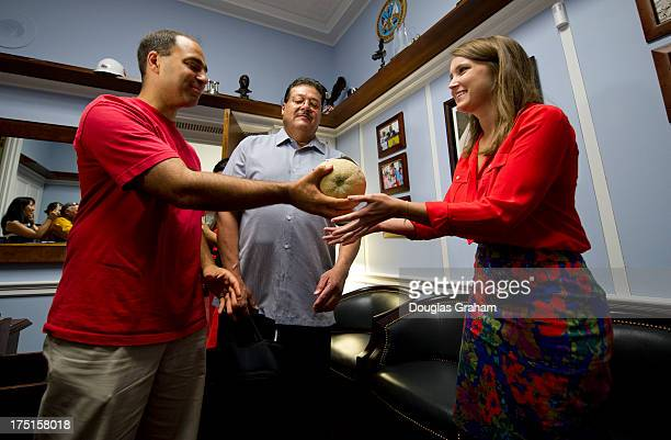 Giev Kashkooli vice president and Ramon Ramirez president of the Farmer Workers United talk with and deliver a cantaloupe picked by migrant workers...