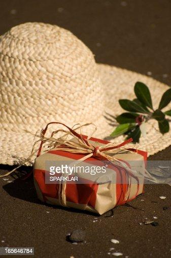 Gift and hat on dark sand beach : Stock Photo