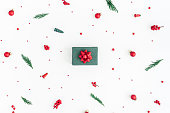 Christmas composition. Gift box, christmas tree branches, red decorations on white background. Flat lay, top view, copy space