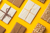Gift boxes packaged with wrapping papers on yellow background. Directly above table top shot. Flat lay presents.