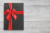 Gift box with red ribbon on white wood view from above, space for text