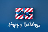 Gift box wrapped in red striped paper and tied with blue bow on dark blue background. Christmas card with inscription Happy Holidays.
