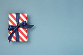 One gift box wrapped in red striped paper and tied with blue bow on blue-gray background. Holiday concept, top view, place for text.