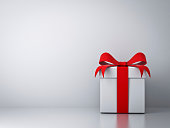 Gift box with red ribbon bow and empty white wall background abstract.