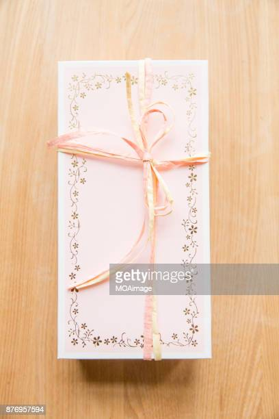 A gift box with some flowers on wooden table