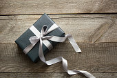 Gift box wrapped in black paper with silver ribbon on wooden surface.
