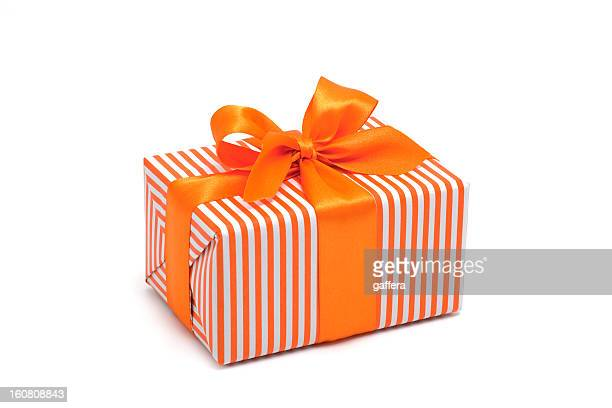 Gift box wrapped in orange stripped paper with an orange bow