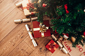 Christmas background with decorations and gift boxes on wooden floor. Beautifully wrapped Christmas gifts and  Christmas crackers placed beside a Christmas tree.