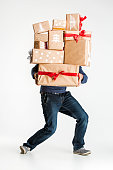 The lot of gift boxes in the hands of young man on white studio background