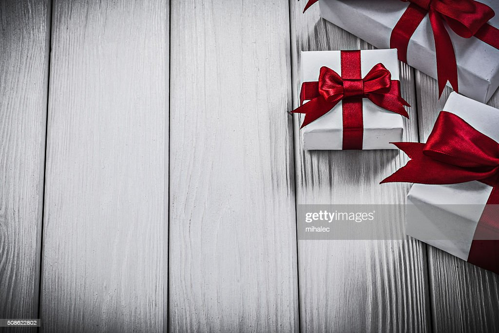 Gift boxes with red bows on wooden board holidays concept : Stock Photo