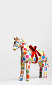 Gift horse with ribbon against white background, close-up