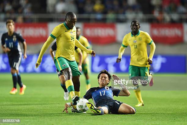 Gift Motupa of South Africa is tackled by Yosuke Ideguchi of Japan during the U23 international friendly match between Japan and South Africa at the...