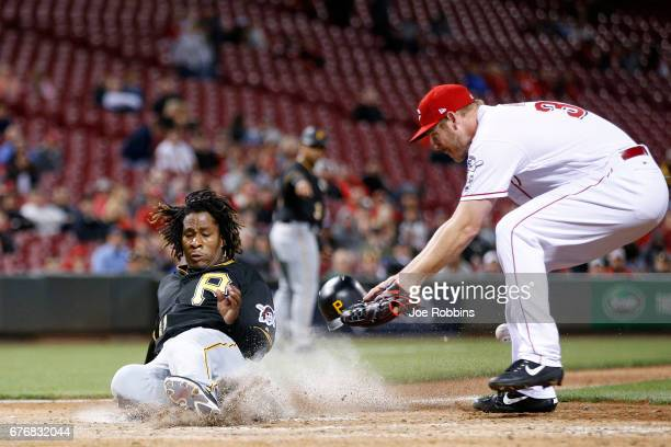 Gift Ngoepe of the Pittsburgh Pirates slides at home plate to score a run after a wild pitch by Blake Wood of the Cincinnati Reds in the seventh...