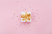 Gift or present box and stars confetti on pink pastel table top view. Flat lay composition for birthday, mother day or wedding. Copy space for text.