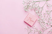 Gift or present box and flower on pink table from above. Pastel color. Greeting card. Flat lay style.