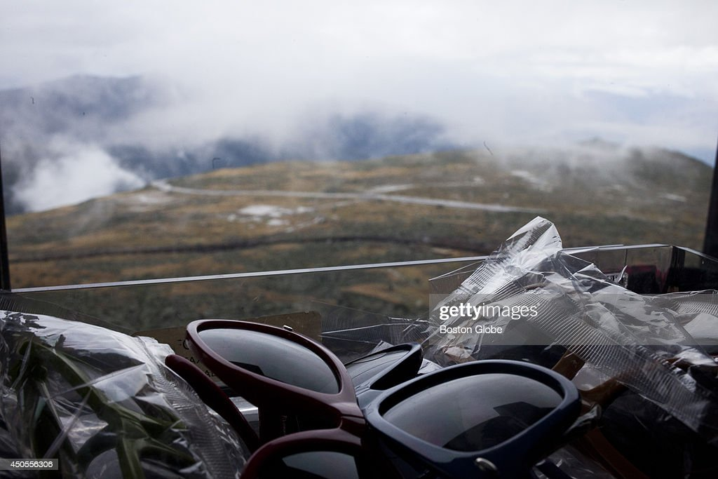 Gift shop sunglasses reflect light on the windowsill overlooking the summit of Mount Washington on Thursday afternoon, June 12, 2014 in the Mt. Washington Observatory in Coos County New Hampshire.