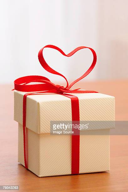 A gift with a heart shaped ribbon on it