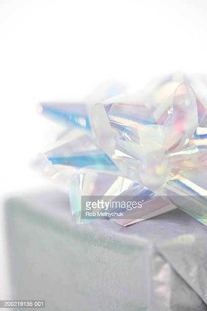 Gift with iridescent bow, close-up (focus on bow)