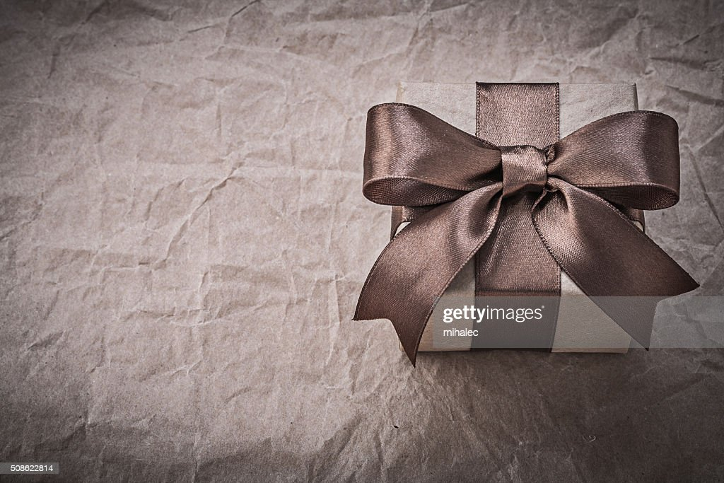 Giftbox with brown bow on wrapping paper holidays concept : Stock Photo