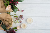 Gifts and flowers on wooden background. Top view, flat lay with lit candles and leaves