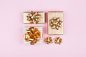Gifts or presents boxes with golden bows on pink pastel background top view. Flat lay composition for birthday, Сhristmas or wedding.