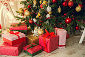 Gifts under a Christmas under spruce on the wooden floor