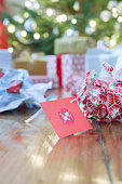 Gifts,  unwrapped paper and gift tag on floor