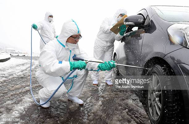 Gifu Prefecture staffs sterilise a vehicle as the avian flu case is detected at a poultry farm on January 15 2017 in Yamagata Gifu Japan